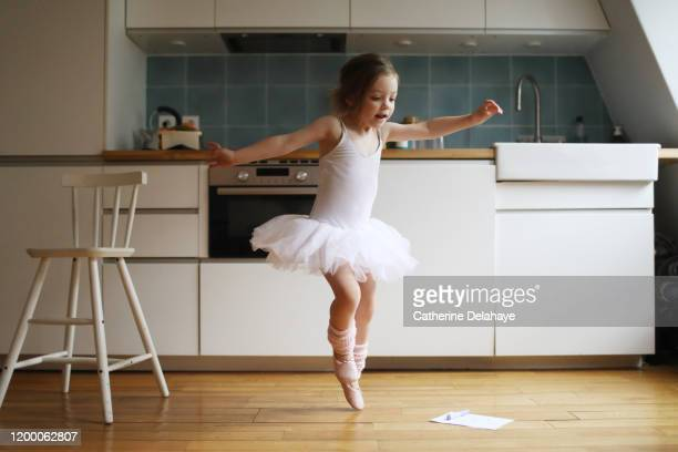 a 4 years old girl dressed as a dancer, dancing in the kitchen - ballet dancer stock pictures, royalty-free photos & images