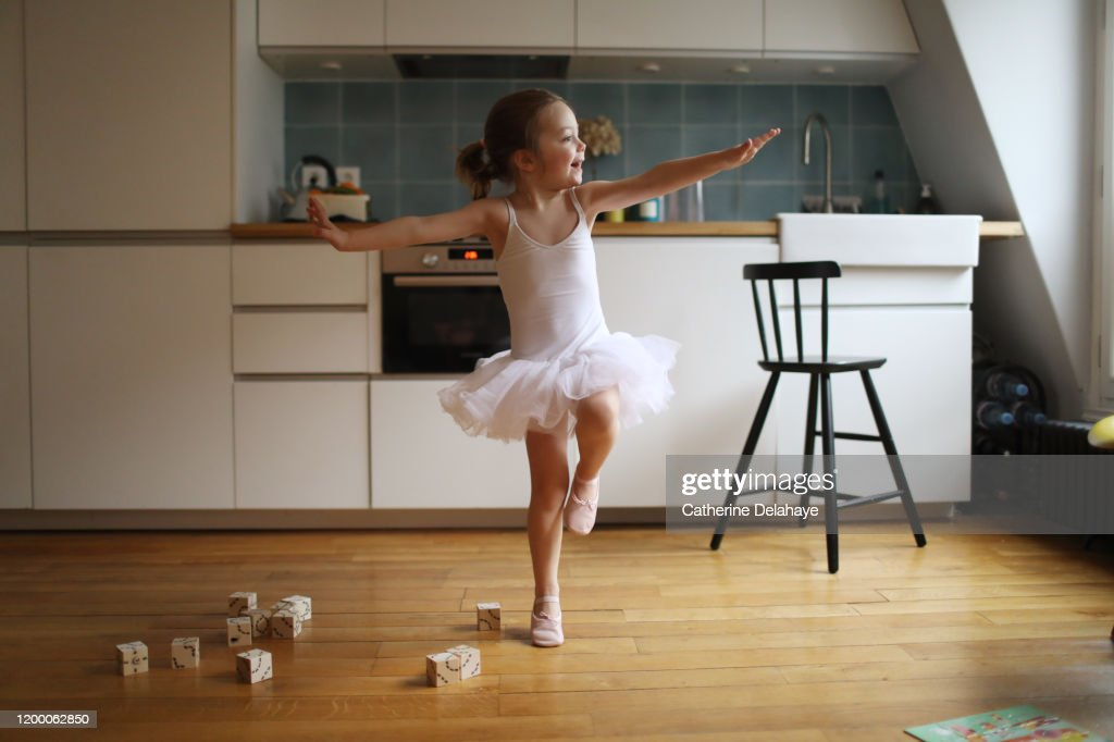 A 4 years old girl dressed as a dancer, dancing in the kitchen : Stock Photo