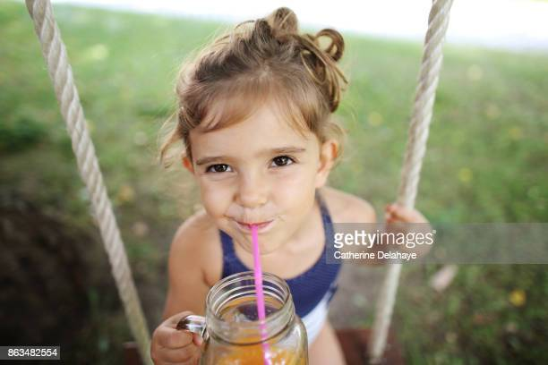 a 3 years old girl drinking orange juice seating on a swing - 2 3 years stock pictures, royalty-free photos & images