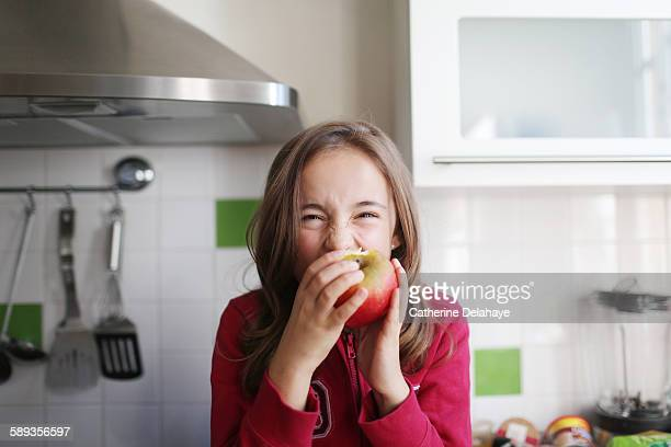 A 10 years old girl eating an apple