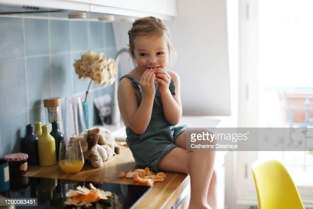 a 4 years old girl eating clementines in the kitchen. - ein mädchen allein stock-fotos und bilder