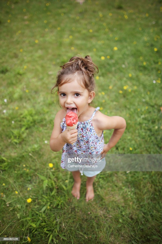 a 3 years old girl eating icecream in the garden ストックフォト