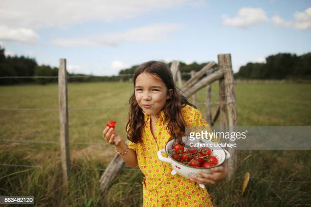 A 8 years old girl eating tomatoes in the countryside