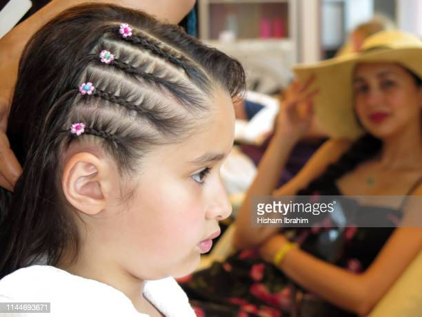 4 years old girl getting her hair braided in a spa hair salon while her mother is watching her. - コーンロウ ストックフォトと画像