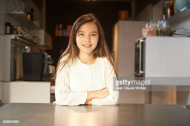 11 years old girl in kitchen looking into camera