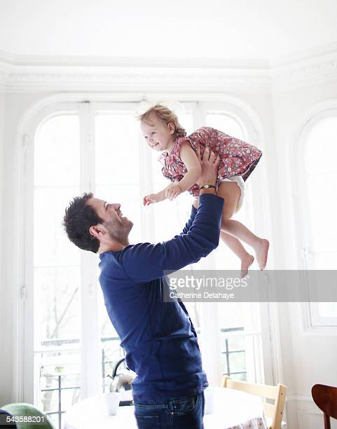 a 2 years old girl in the arms of her daddy - diaper girl photos et images de collection