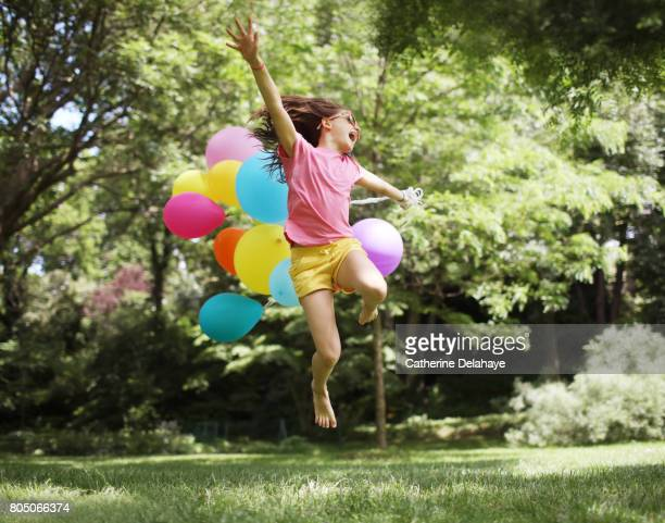 A 10 years old girl jumping with balloons in a park