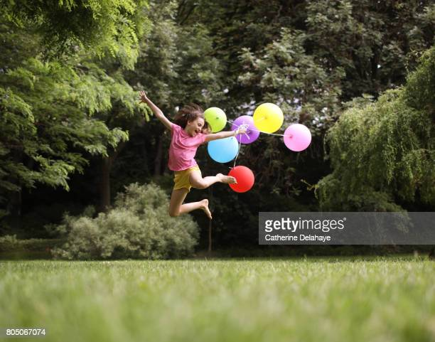 a 10 years old girl jumping with balloons in a park - 10 11 years stock pictures, royalty-free photos & images
