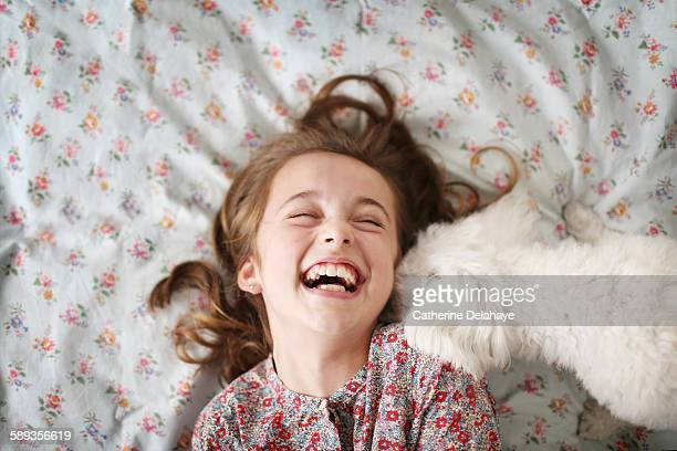 a 10 years old girl laughing with her dog - variable schärfentiefe stock-fotos und bilder