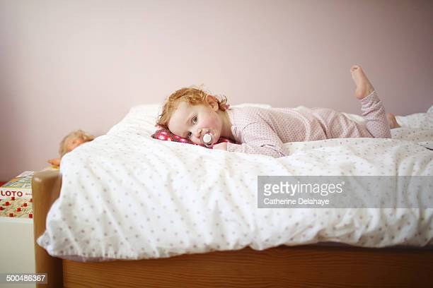 A 3 years old girl laying on her bed