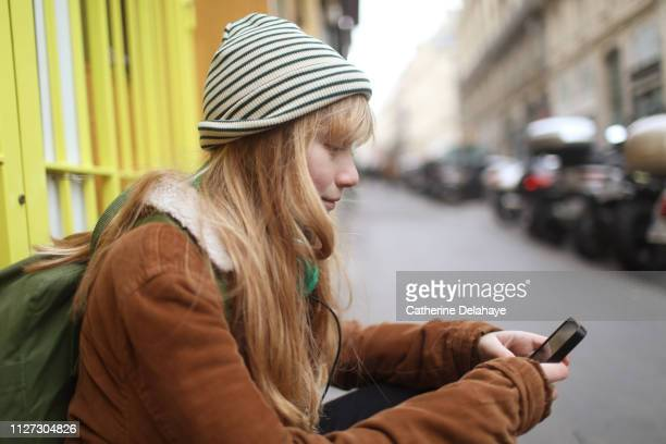 A 12 years old girl looking at his cell phone in the streets of Paris