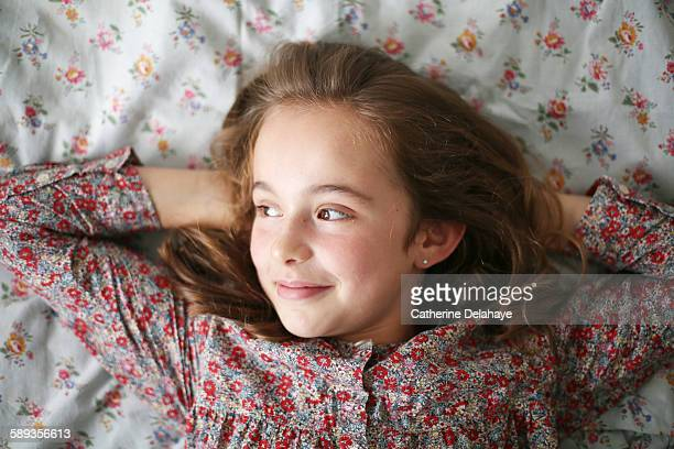 a 10 years old girl lying on her bed - 10 11 years stock photos and pictures