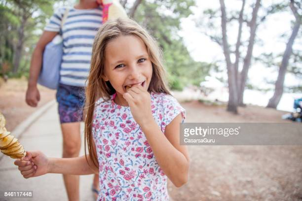 6 years old girl on a summer holiday enjoy eating fried potato slices on stick - 6 7 years stock pictures, royalty-free photos & images