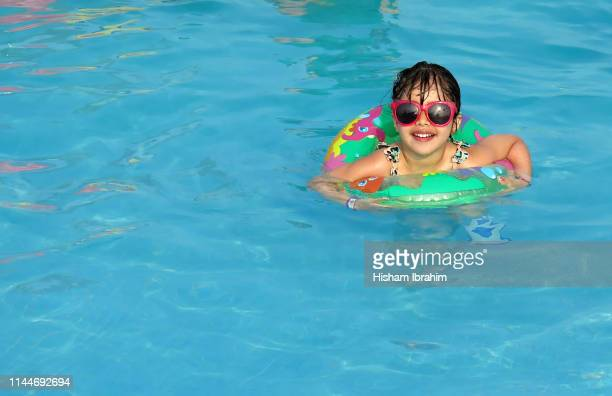 4 years old girl on vacation swimming in pool with green inflatable ring. - 4 5 years stock pictures, royalty-free photos & images