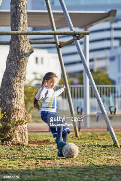7 years old girl playing football in the park