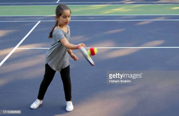 7 years old girl playing tennis and hitting a ball with the racket. - 6 7 years stock pictures, royalty-free photos & images