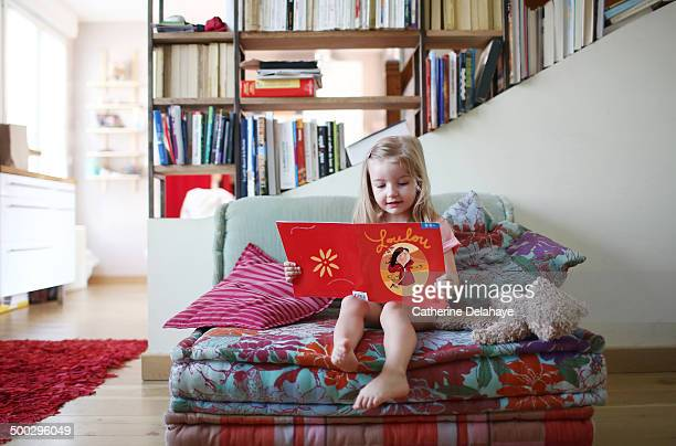 a 3 years old girl reading a book on a sofa - 2 3 years stock pictures, royalty-free photos & images