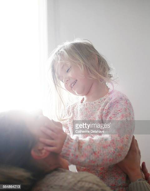A 3 years old girl smiling to her mum