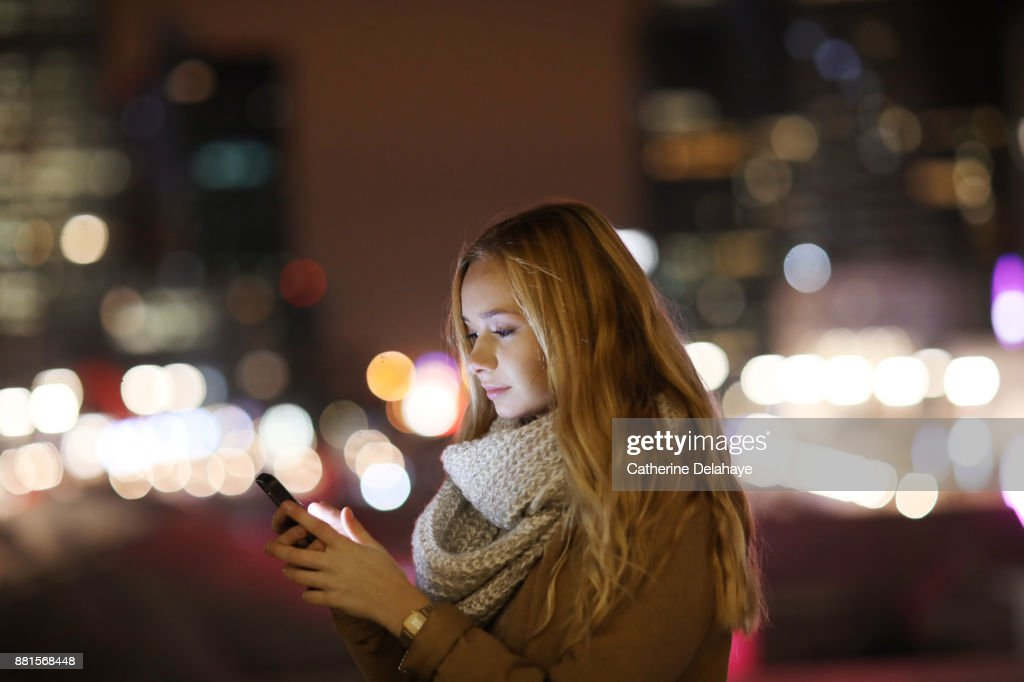 A 17 years old girl with a phone in town by night : Stock Photo