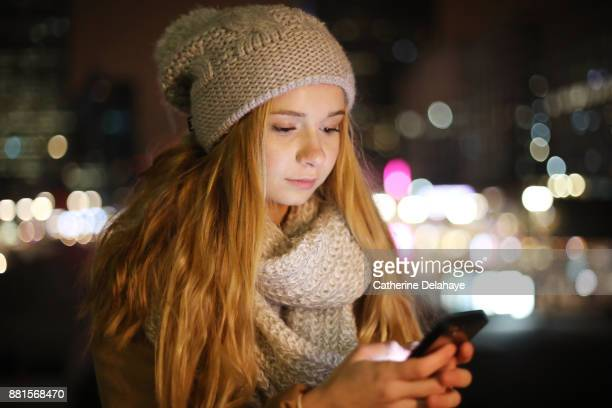 A 17 years old girl with a phone in town by night