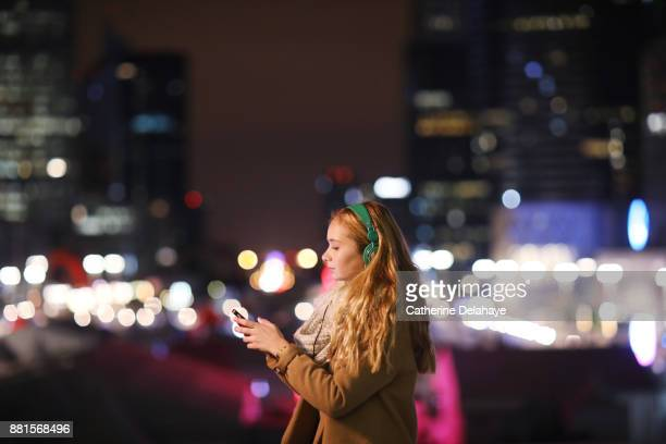 a 17 years old girl with a phone in town by night - 16 17 years stock pictures, royalty-free photos & images