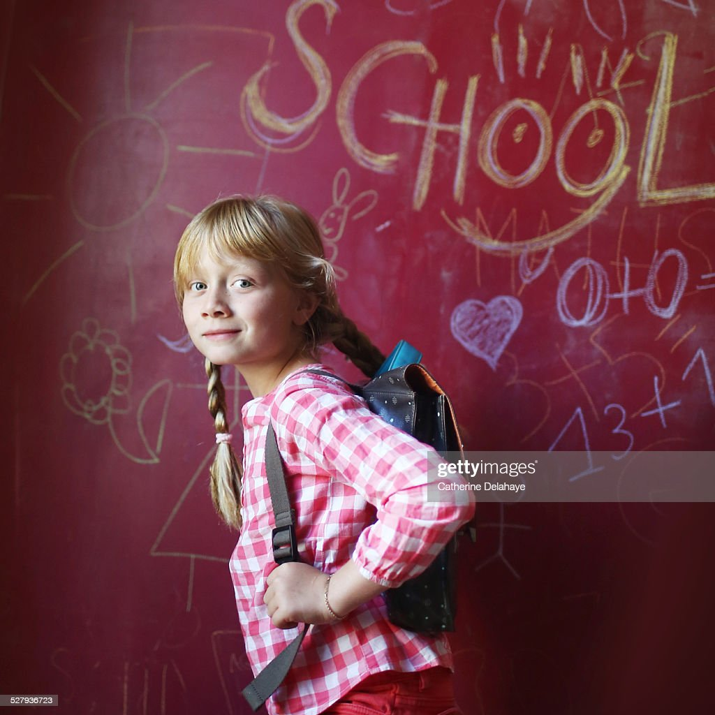 A 8 years old girl with a schoolbag : Stock Photo