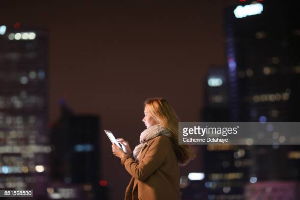 a 17 years old girl with a tablet in town by night - 16 17 years photos stock photos and pictures