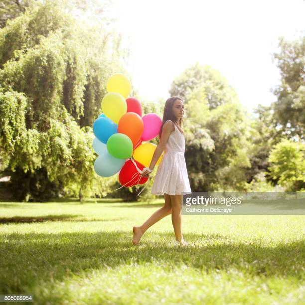 a 10 years old girl with balloons in a park - 10 11 years stock pictures, royalty-free photos & images