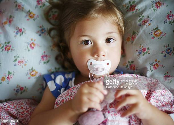 A 2 years old girl with her dummy in her bed