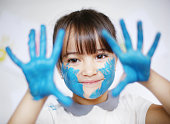 A 4 years old girl with paint on her hands
