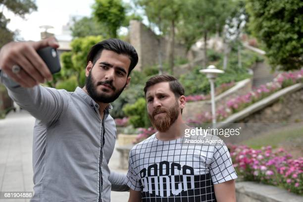 25 years old Iranian Lionel Messi lookalike university student Reza Parastesh poses for a photo with a man in Tehran Iran on May 11 2017 Reza grew a...