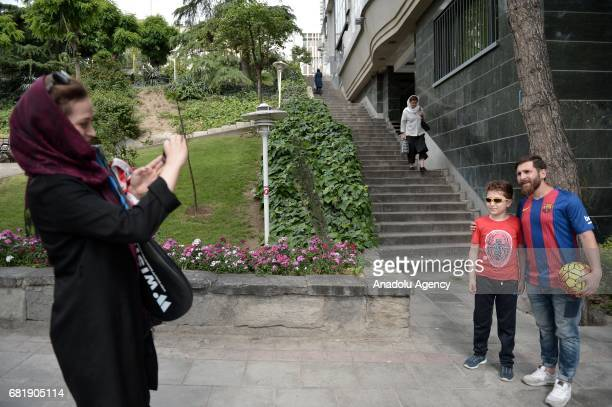 25 years old Iranian Lionel Messi lookalike university student Reza Parastesh poses for a photo with a kid fan while kid's mother take their photo in...