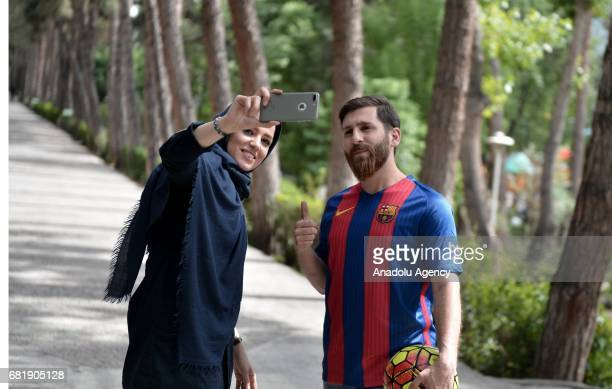 25 years old Iranian Lionel Messi lookalike university student Reza Parastesh poses for a photo with a woman in Tehran Iran on May 11 2017 Reza grew...