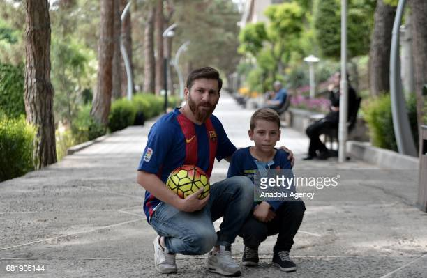 25 years old Iranian Lionel Messi lookalike university student Reza Parastesh poses for a photo with a kid fan in Tehran Iran on May 11 2017 Reza...