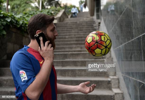 25 years old Iranian Lionel Messi lookalike university student Reza Parastesh speaks on the phone as he plays with a soccer bal in Tehran Iran on May...