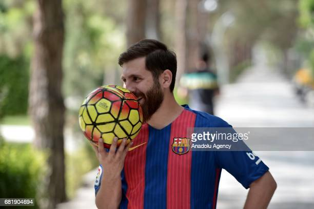25 years old Iranian Lionel Messi lookalike university student Reza Parastesh gestures while holding a soccer ball in Tehran Iran on May 11 2017 Reza...