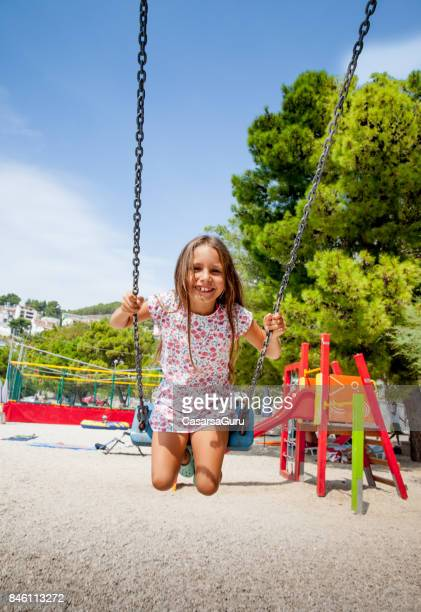 6 years old joyful girl on beach holiday using swing at the playground - 6 7 years stock pictures, royalty-free photos & images
