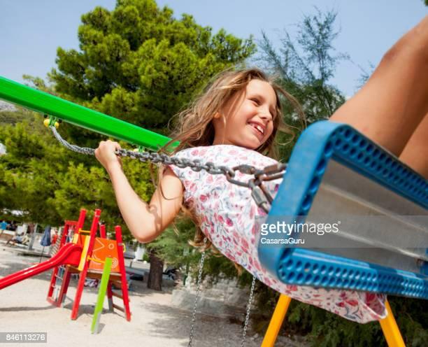 6 Years Old Joyful Girl On Beach Holiday Using Swing At The Playground