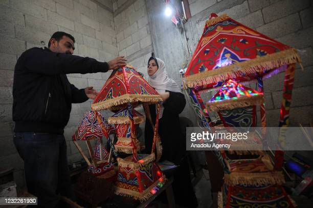 Years old Kader, wife of Halit Zendah, adjusts a handmade decoration for holy Islamic fasting month of Ramadan in Khan Yunis, Gaza on April 10, 2021....