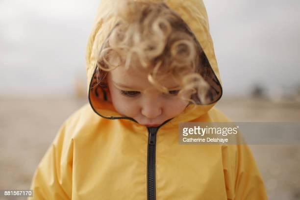 A 2 years old little girl wearing a oilkin on the beach