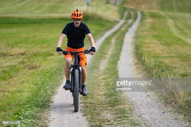 46 years old man cycling electric mountain bike in rural landscape