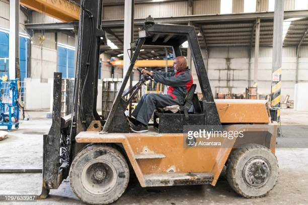 55-60 years old man driving forklift in concrete factory. cordoba, spain. - 55 59 years stock pictures, royalty-free photos & images