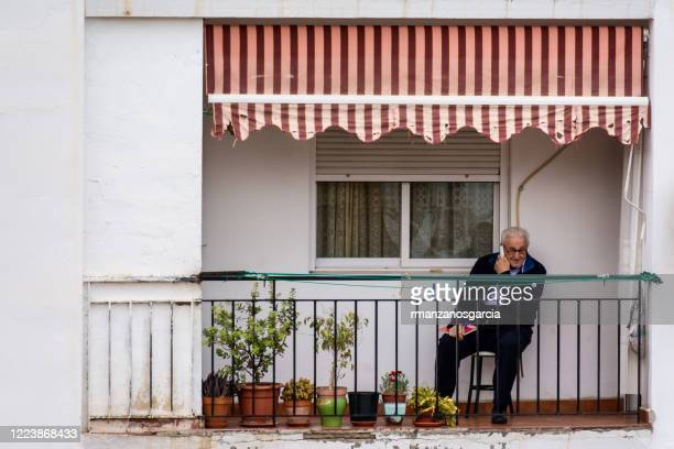 80 years old man talking on the phone on the terrace during the confinement by the covid-19 - state of emergency stock pictures, royalty-free photos & images