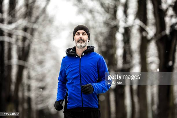 45 years old man with beard running in alley on cold winter day