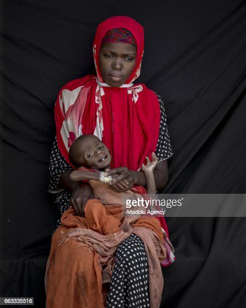 20 years old Maryam Adam Abdi fled from Samakay district 40 kilometers away from Bay due to drought holds her son Mohamed Adam Mukhtar who receives...
