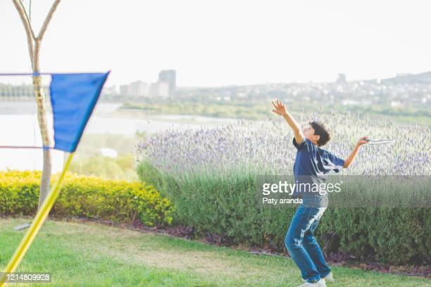 13 years old mexican boy playing badminton in a beautiful garden at leon, gto. mexico. - 12 13 years stock pictures, royalty-free photos & images
