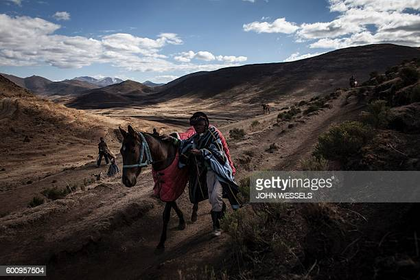 16 years old Mosotho jockey Mokikeng Tladi walks his horse down to the race track on July 16 2016 in Semonkong Horseracing in the mountain kingdom of...