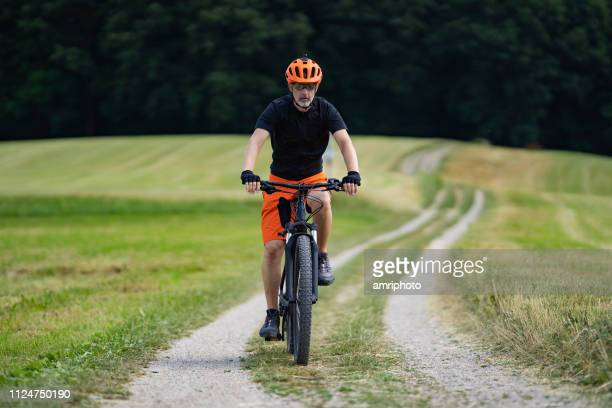 45 years old mountainbiker cycling alone with electric bike on rural gravel road