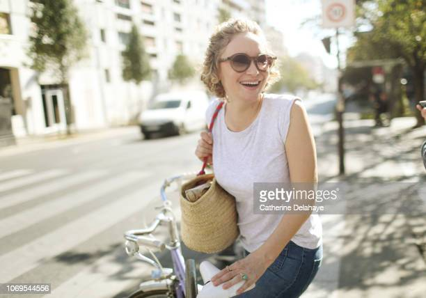A 40 years old parisian woman with her bike in the streets of Paris