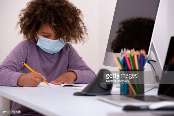 6 years old school child writing with a pencil, wearing a face mask. homeschooling during covid 19 epidemic. - 6 7 years stock pictures, royalty-free photos & images
